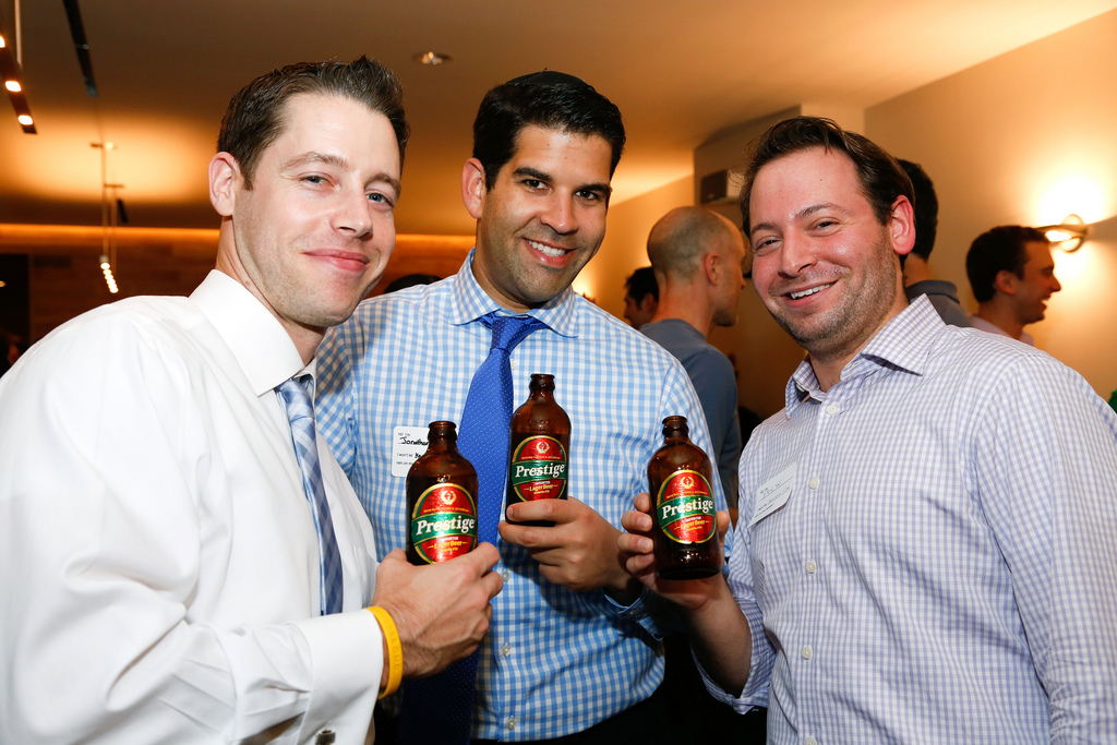 Three men toasting during opening party
