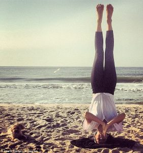 Hilaria Baldwin practicing a headstand with no hands on beach