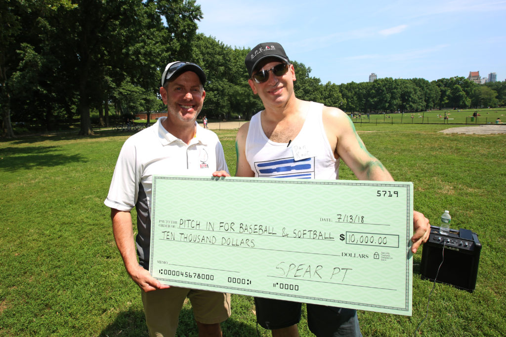 CEO and co-founder Dan Rootenberg donating funds to Pitch in Baseball with giant check