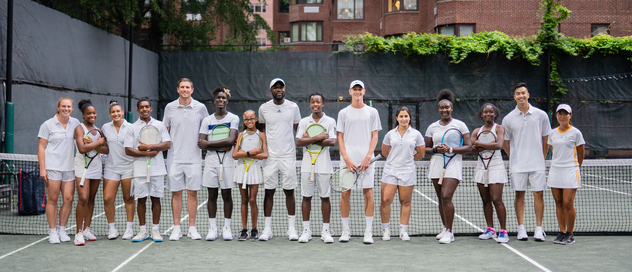 Group of tennis players smiling for a photo on the field