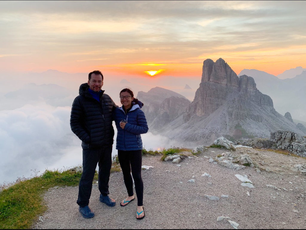 Father and daughter on a mountain surrounded by clouds and a sunset