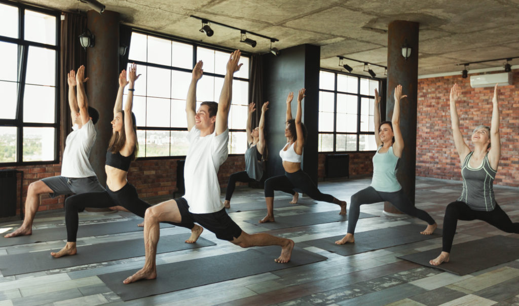 group of people practicing yoga in a sunlit room