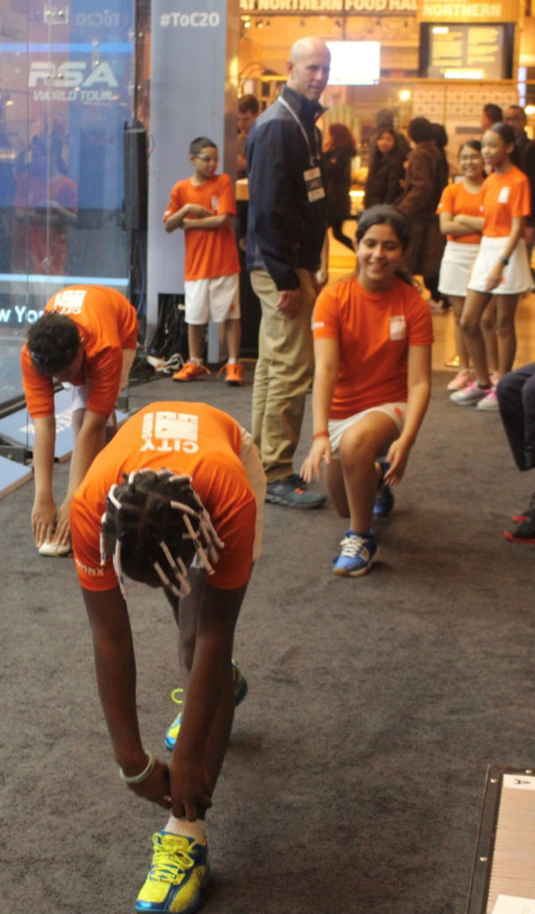 young squash players lunging as part of a warm up